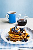 Vegan sweet potato pancakes with blueberries, maple syrup and coconut chips