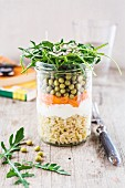 A layered salad with rocket, peas, grated carrot and soft wheat in a glass