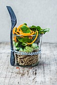 Spaghetti salad with cucumber, spinach and spiralized carrot in a glass