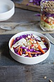 Salad with chicken, carrot, apple, red cabbage, kale and sunflower seeds