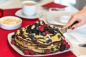 A pancake cake with berries and chocolate sauce being sliced