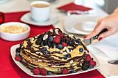 Pfannkuchentorte mit Beeren und Schokoladensauce anschneiden