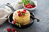 Gestapelte Buttermilchpancakes mit Himbeeren und Kokosnuss zum Frühstück