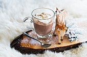 Hot chocolate in a glass cup with wood-carved deer figures