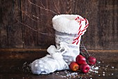A Christmas boot with apples and candy canes