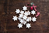 Cinnamon stars and a red bauble on a wooden background