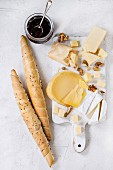 Cheese plate, assortment of cheese with walnuts, jam and bread on white wood serving board