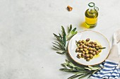 Pickled green Mediterranean olives in virgin olive oil on white ceramic plate, olive tree branch