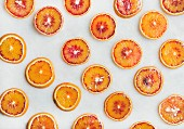 Fresh juicy blood orange slices over light marble table background, top view