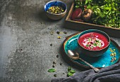 Spring detox beetroot soup with mint, chia, flax and pumpkin seeds on blue ceramic plate