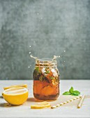 Summer cold Iced tea with fresh bergamot, mint and lemon in glass jar with splashes on light table