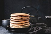Stack of homemade american ombre chocolate pancakes served on black plate with jug of cream and teapot