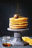 Stack of homemade american ombre yellow turmeric pancakes with honey sauce served on cake stand