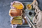 Variety of sliced american ombre chocolate, green tea matcha and turmeric pancakes with honey sauces