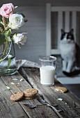 Ein Glas Milch und Kekse auf rustikalem Holztisch