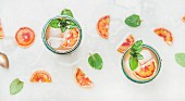 Blood orange fresh summer lemonade with ice and mint in glasses, light grey marble background