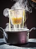 Dampfende gekochte Pasta im Siebeinsatz über Topf abtropfen lassen