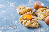 Fresh raw uncooked homemade twisted pasta tagliatelle with egg yolk, shell and pasta cutter