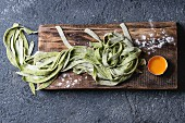 Fresh raw uncooked homemade green spinach pasta tagliatelle with egg yolk and flour