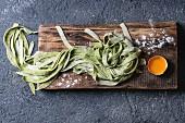 Frische selbstgemachte Spinat-Tagliatelle und ein Eigelb auf Holzbrett