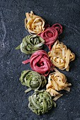 Variety of colored fresh raw uncooked homemade pasta tagliatelle green spinach, pink beetroot and traditional yellow