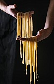 Fresh raw uncooked homemade pasta tagliatelle in man s hands over black apron as background