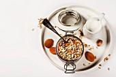 Haferflockenmüsli mit Trockenfrüchten und Nüssen in Bügelglas auf Tablett (Aufsicht)
