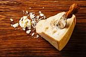 Ein Sttück Parmesankäse mit Käsemesser auf Holzuntergrund