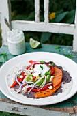 Tortilla mit schwarzer Bohnenpaste, gebratener Paprika, Süsskartoffeln, Avocado, Mais, roten Zwiebeln und Minz-Joghurt-Sauce