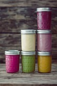Glass jars of different coloured smoothies