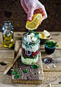 Lemon juice being squeezed on a millet and feta salad with beetroot and parsley in a glass jar