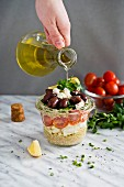 Olive oil being poured over a quinoa salad with feta, tomatoes and kalamata olives in a glass jar