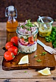 Bulgur salad with tuna, red onion and tomatoes in a glass jar