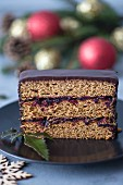 Slice of a gingerbread cake with plum jam and chocolate ganache