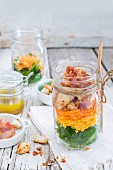 Colourful salad with vegetables, bacon, cheddar, croutons and lemon and honey dressing in a glass jar