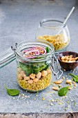 Quinoa curry with baby leaf spinach, chickpeas and red onion in a glass jar