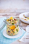 Quinoa salad with orange, chickpeas and lingonberries in a glass jar