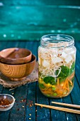 Vegan noodle soup with vegetables and tofu in a glass jar