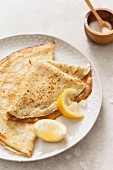Two folded pancakes on an off white texture plate with lemon wedges on a stone surface
