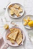 Two plates of folded and rolled pancakes served with lemon wedges on white linen covered table and water glasses