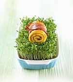 A rolled pancake with bacon on a bed of cress for Easter