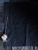 Antiker Löffel mit Puderzucker auf dunkelblauem Stoffgrund