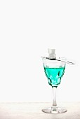 Absinthe with an absinthe spoon and sugar cubes in a crystal glass