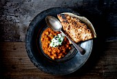 Chana Masala (Indian chickpea curry) on a tin plate with chapati and yoghurt dip