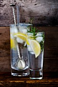 Gin and tonic with lemon, ice cubes and rosemary