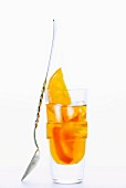 A glass of Amaro Nonino, an Italian herbal liqueur, with ice cubes and orange slices