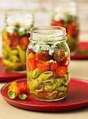 Pasta salad with pesto and cherry tomatoes in a glass jar