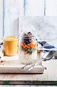 Rice salad in a glass jar with mung bean seedlings, peas, carrots and rosemary with a Thai peanut and chilli sauce (Vegan)
