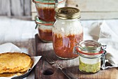 Chilli con carne with rice and guacamole with sour cream in glass jars