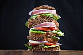 Fresh Tuna Steak Sandwich stacked with lettuce, tomato and cucumber on sliced astisan bread